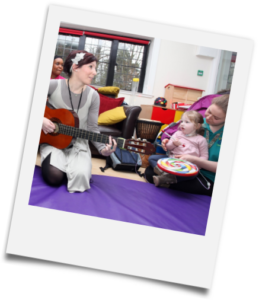 Children and carers taking part in a music therapy session