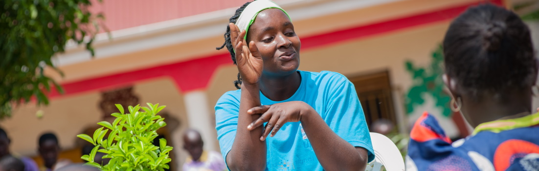 A Volunteer teaches a family how to communicate using sign language; courtesy of SignHealth Uganda